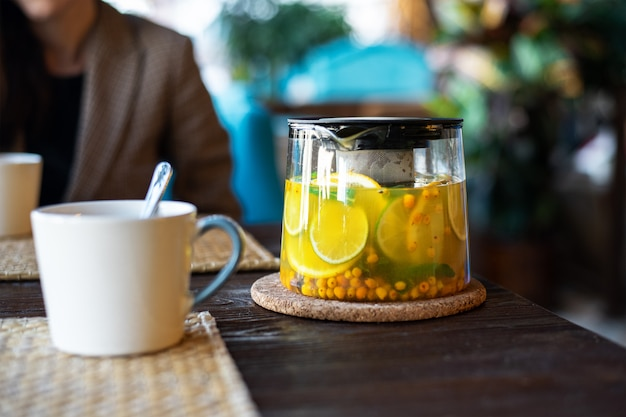 Glass teapot with tea from sea buckthorn, lemon, mint and herbs on a wooden table with a cup on a blurred