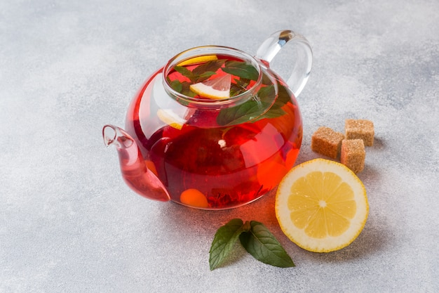 Glass teapot with tea, mint and lemon on grey table with copy space