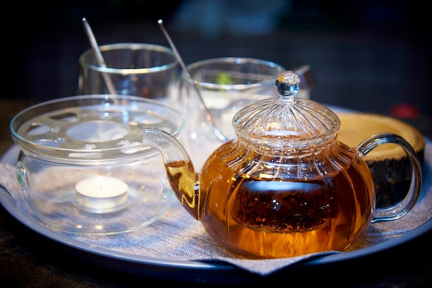 Glass teapot with tea on a tray with cups close-up.