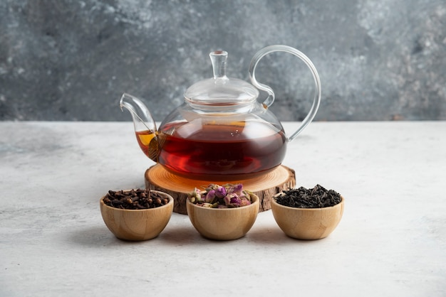 A glass teapot with wooden bowls of loose teas.
