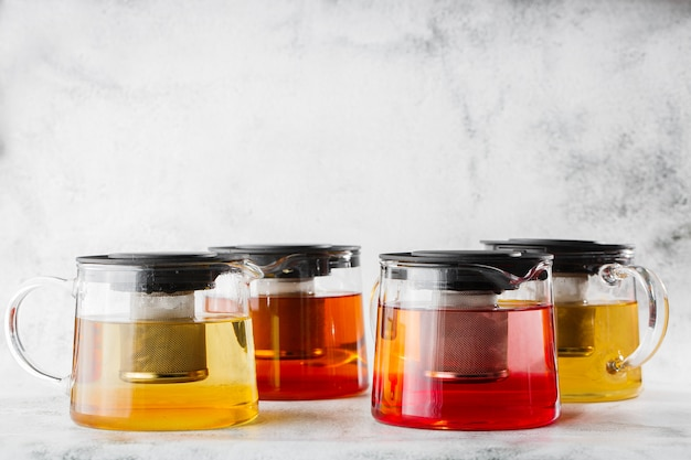 4種類のお茶が入ったガラスのティーポット。明るい大理石の背景に分離された紅茶、緑茶。俯瞰、コピースペース。カフェメニューの宣伝。コーヒーショップメニュー。横の写真。