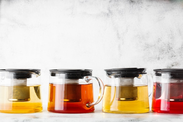 Glass teapots with four kinds of tea. black tea, green tea isolated on bright marble background. overhead view, copy space. advertising for cafe menu. coffee shop menu. horizontal photo.