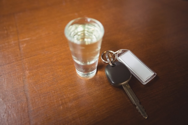 Glass of tequila shot with car key in bar counter