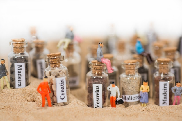 Glass test-tube with sand of different summer vacation destinations. located in sand with small people figures.