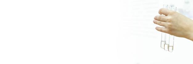 Стеклянные пробирки в руках и пробирки с образцами крови для медицинских анализов на белоснежном лабораторном стенде. судмедэксперт держит пробирку с образцом днк. тест на отцовство. баннер.
