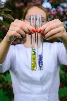 花のサンプルが入ったガラス製試験管、クローズアップ。フラスコを保持している女性の手がぼやけています。植物、薬草、自然の花の香りの研究。広告香水業界。