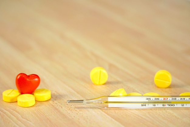 Glass thermometer with yellow medicines and mini red heart on wood table.