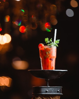 A glass of tomato drink with parsley