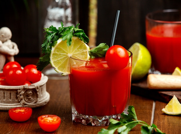 A glass of tomato juice garnished with cherry tomato lemon and parsley