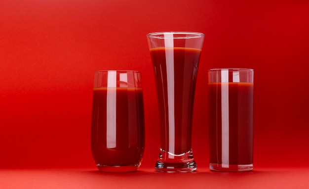 Glass of tomato juice isolated on red