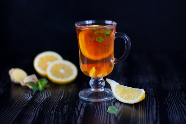 Glass transparent cup of tea with lemon, ginger and mint