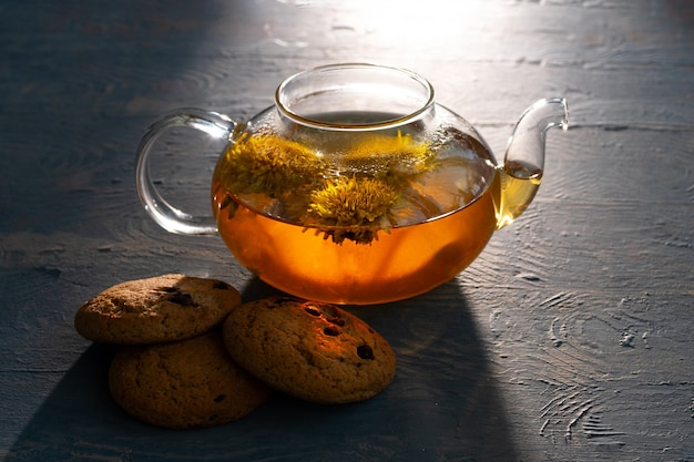Glass transparent teapot with healthy herbal tea from yellow dandelions and oatmeal cookies with raisins on a blue wooden background, illuminated by the sun, low key. tea day concept
