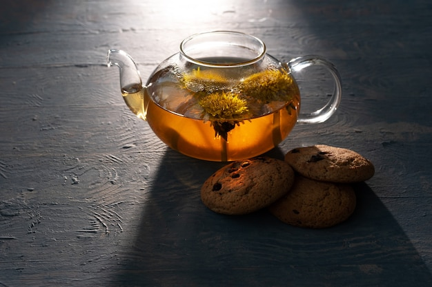 Glass transparent teapot with healthy herbal tea from yellow dandelions and oatmeal cookies with raisins on a blue wooden background, illuminated by the sun, low key.