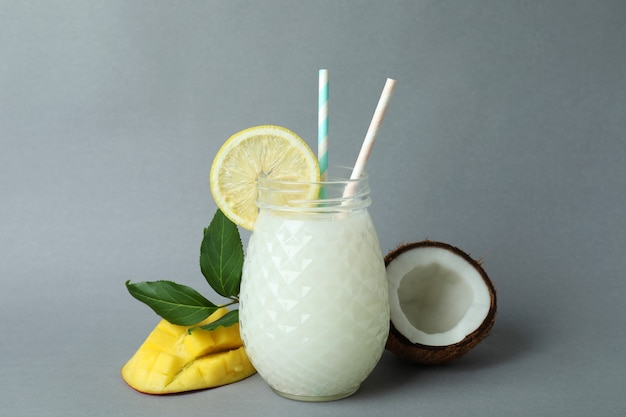 Glass of tropical cocktail and ingredients on gray background