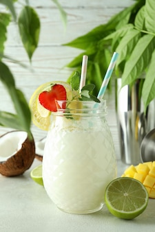 Glass of tropical cocktail and ingredients on white textured table