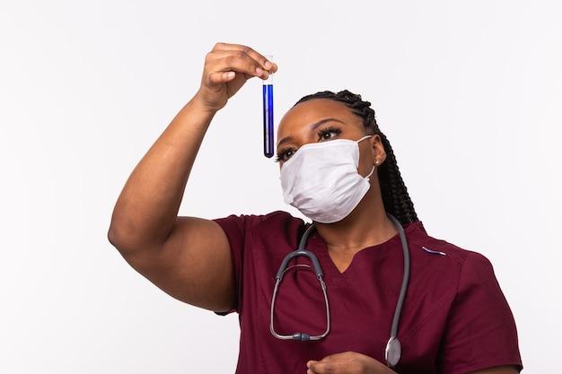 Стеклянная трубка с голубой жидкостью в руке медсестры во время медицинского обследования. разработка вакцины.