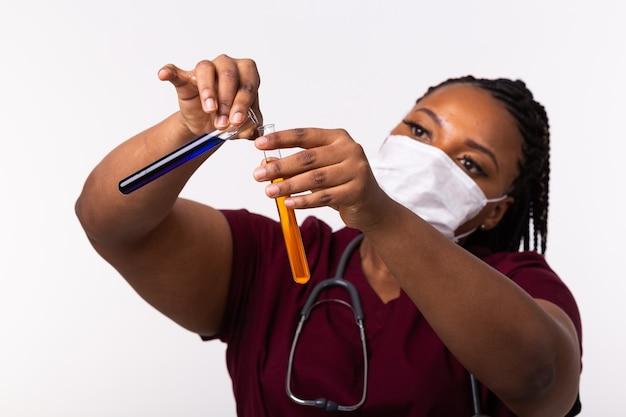 Стеклянные пробирки с жидкостями в руке медсестры во время медицинского обследования.