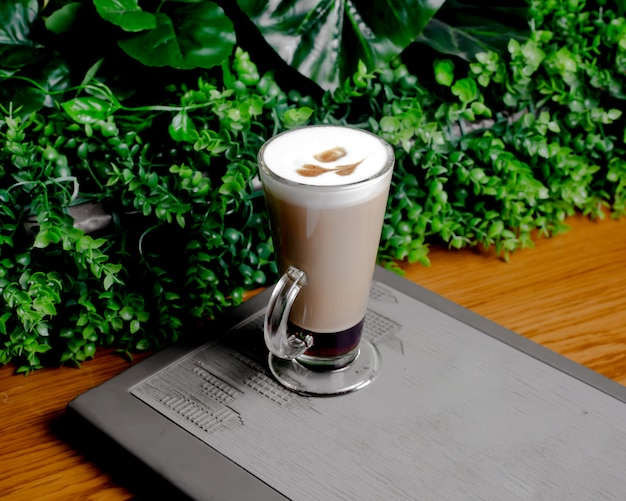 A glass of two layered coffee with heart latte art on top