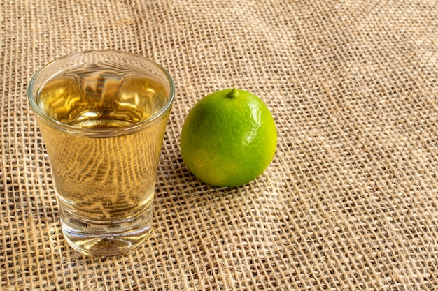 Glass of typical brazil drink cachaca in jute fabric with whole lemon