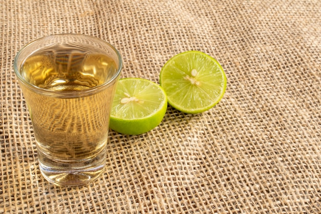 Glass of typical brazilian drink cachaca in jute fabric with cut lemon