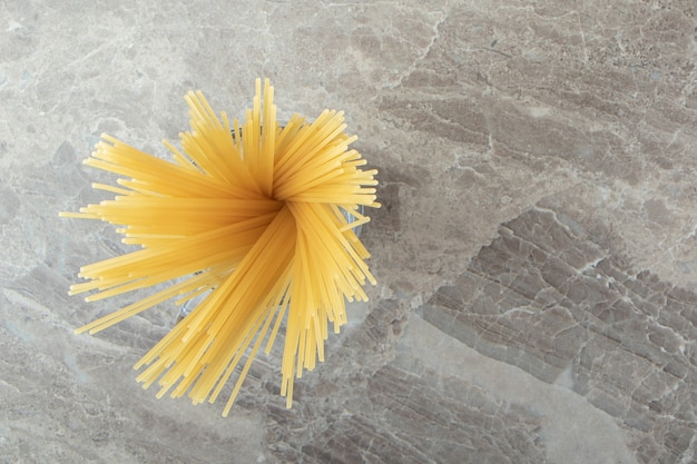 Glass of uncooked spaghetti on marble surface