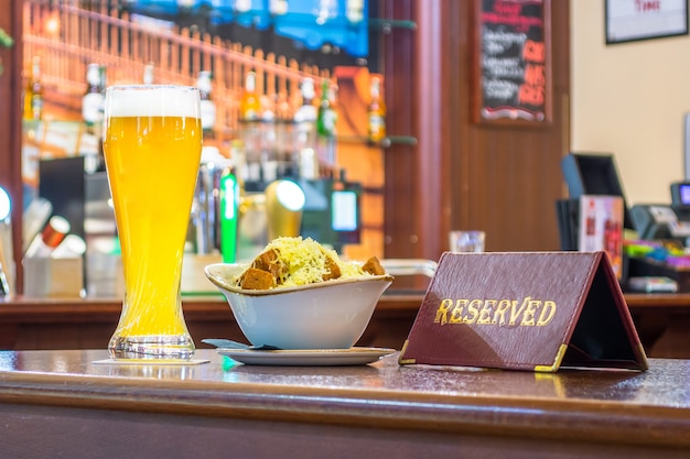 A glass of unfiltered beer with rusks cheese, a tablet - is reserved on a wooden table in the restaurant bar.