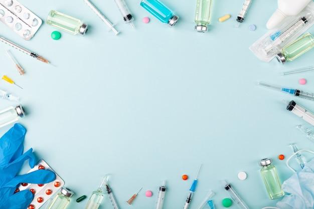 青色の背景にガラス ワクチン、アンプル ボトル、手袋、注射器の針、錠剤
