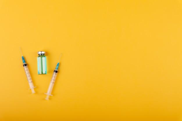 Glass vaccine bottle with syringe needles on yellow background