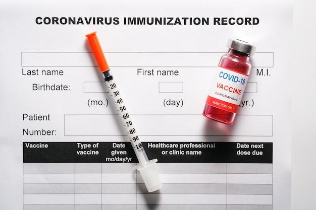 Стеклянный флакон с вакциной и шприц для вакцинации от covid-19