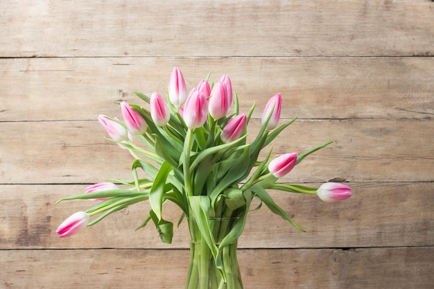 Glass vase and a bouquet of pink tulips on wooden. concept of the holiday and the beginning of spring.