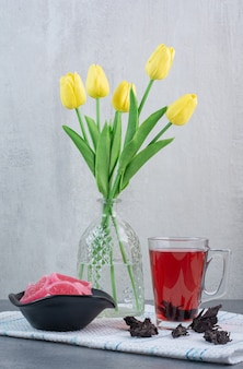 A glass vase of flowers with cup of tea and marmalade.