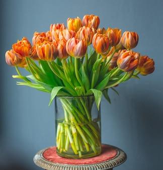 A glass vase of orange color tulips.