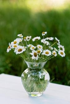 Стеклянная ваза с букетом цветов ромашки летом на открытом воздухе.