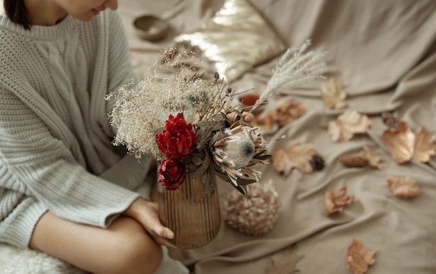 Glass vase with autumn flowers in female hands on a blurred background with autumn leaves.