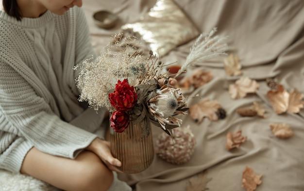 가을 잎이 있는 흐릿한 배경에 여성의 손에 가을 꽃이 있는 유리 꽃병.