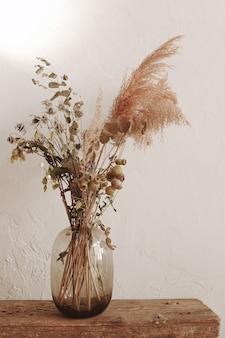 Стеклянная ваза с сухими растениями на белой стене минималистичное украшение дома