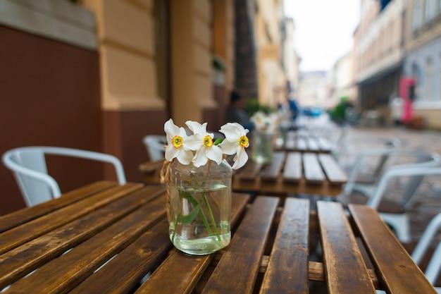 通りのレストランの木製のテーブルに花とガラスの花瓶。居心地のよさを生み出すインテリアのディテール
