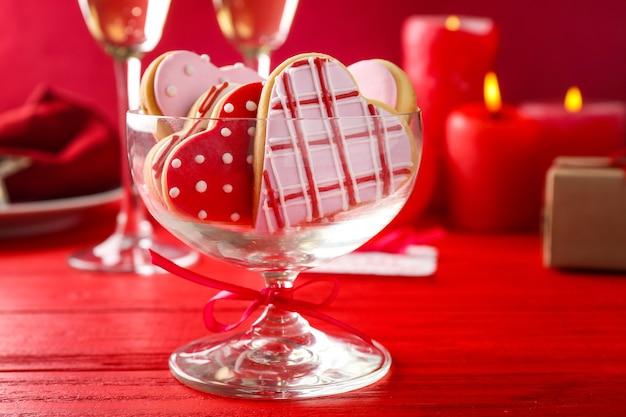 赤い木製の背景にハート型の艶をかけられたクッキーとガラスの花瓶