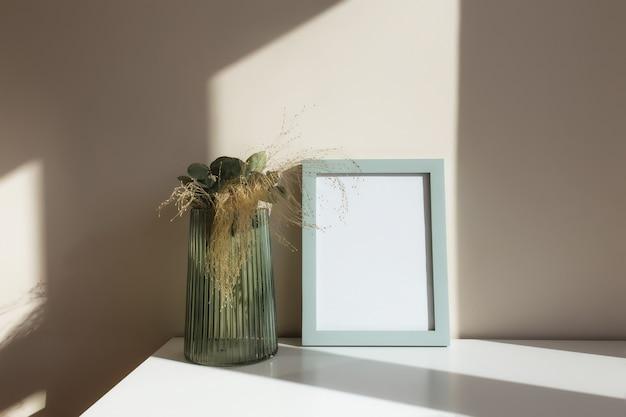 Стеклянная ваза с гербарными цветами, ветками эвкалипта, пустыми белыми рамками для фотографий на белом столе в интерьере с бежевыми стенами у окна.
