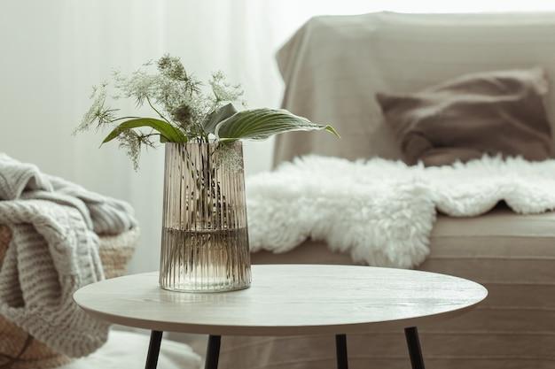 스칸디나비아 스타일의 흐릿한 거실 배경에 대해 테이블 위에 식물이 있는 유리 꽃병.