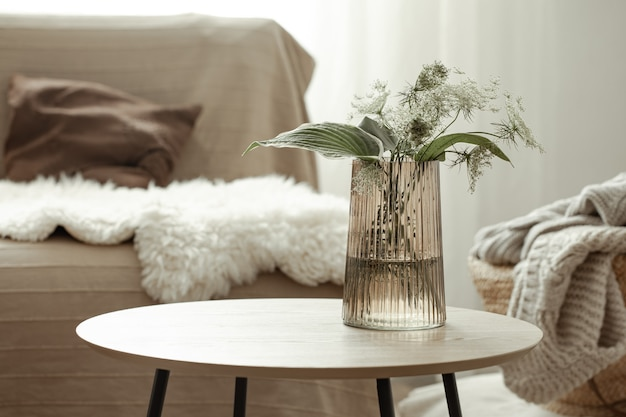 Glass vase with plants on the table against the blurred background