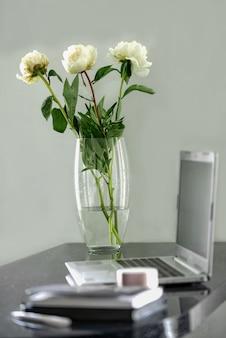ラップトップを開いて作業場所に立つ白い牡丹のガラス花瓶