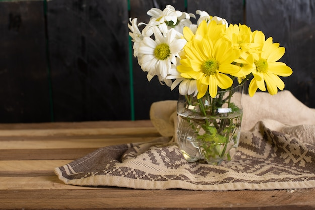A glass vase of yellow and white flowers
