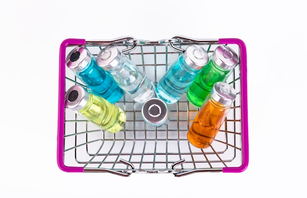 Glass vials of different colors for the vaccine in the shopping cart on a white background. copy space. selective focus.