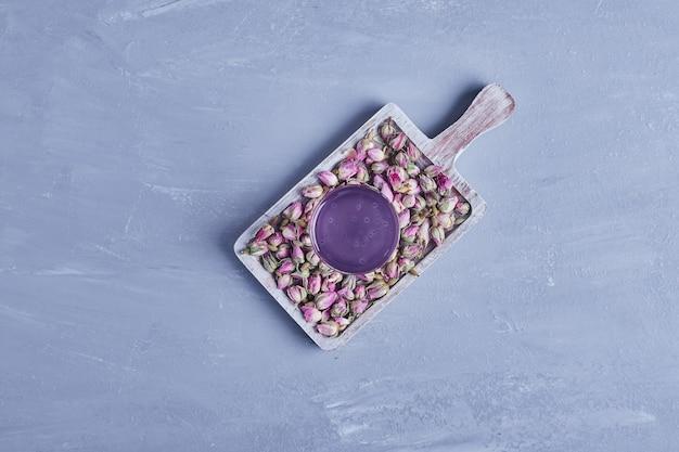 Un bicchiere di succo di violetta con boccioli di fiori in un piatto di legno, vista dall'alto.