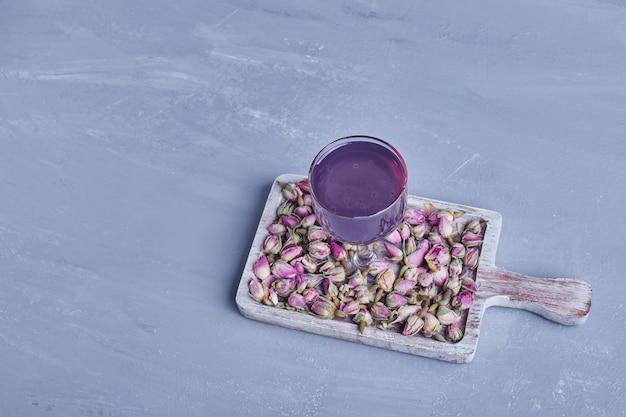 Un bicchiere di succo di violetta con boccioli di fiori in un piatto di legno.