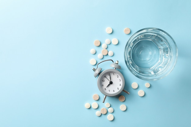 Glass of water, alarm clock and pills isolated