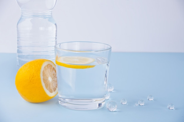 Glass of water, bottle and lemon fruit on the blue table.