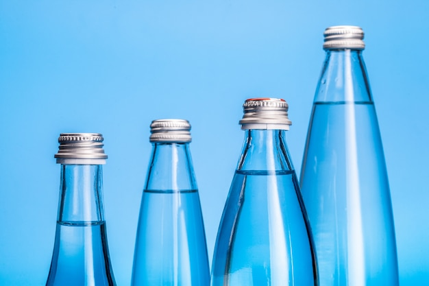Glass water bottles on a light blue background