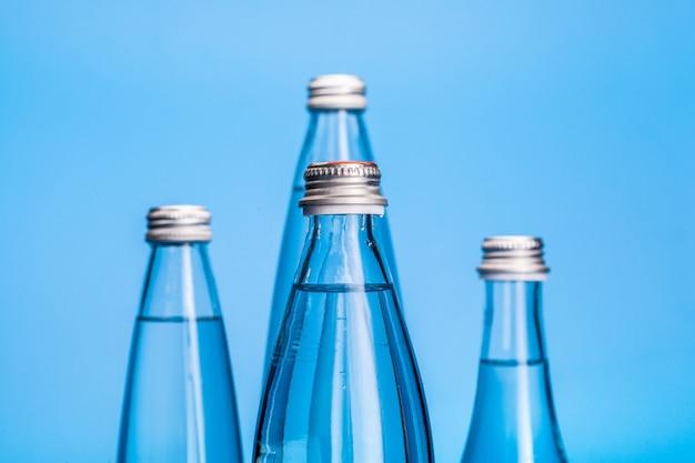 Glass water bottles on a light blue